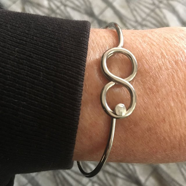 stainless steel infinity sign shown on wrist