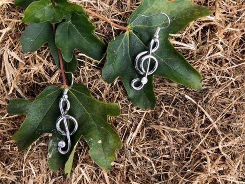Miniature Treble Clef Earrings shown on leaf