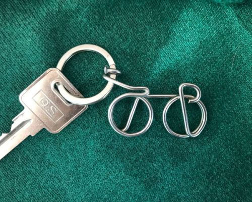 bike keyring hokey spokey shownn with key on green background